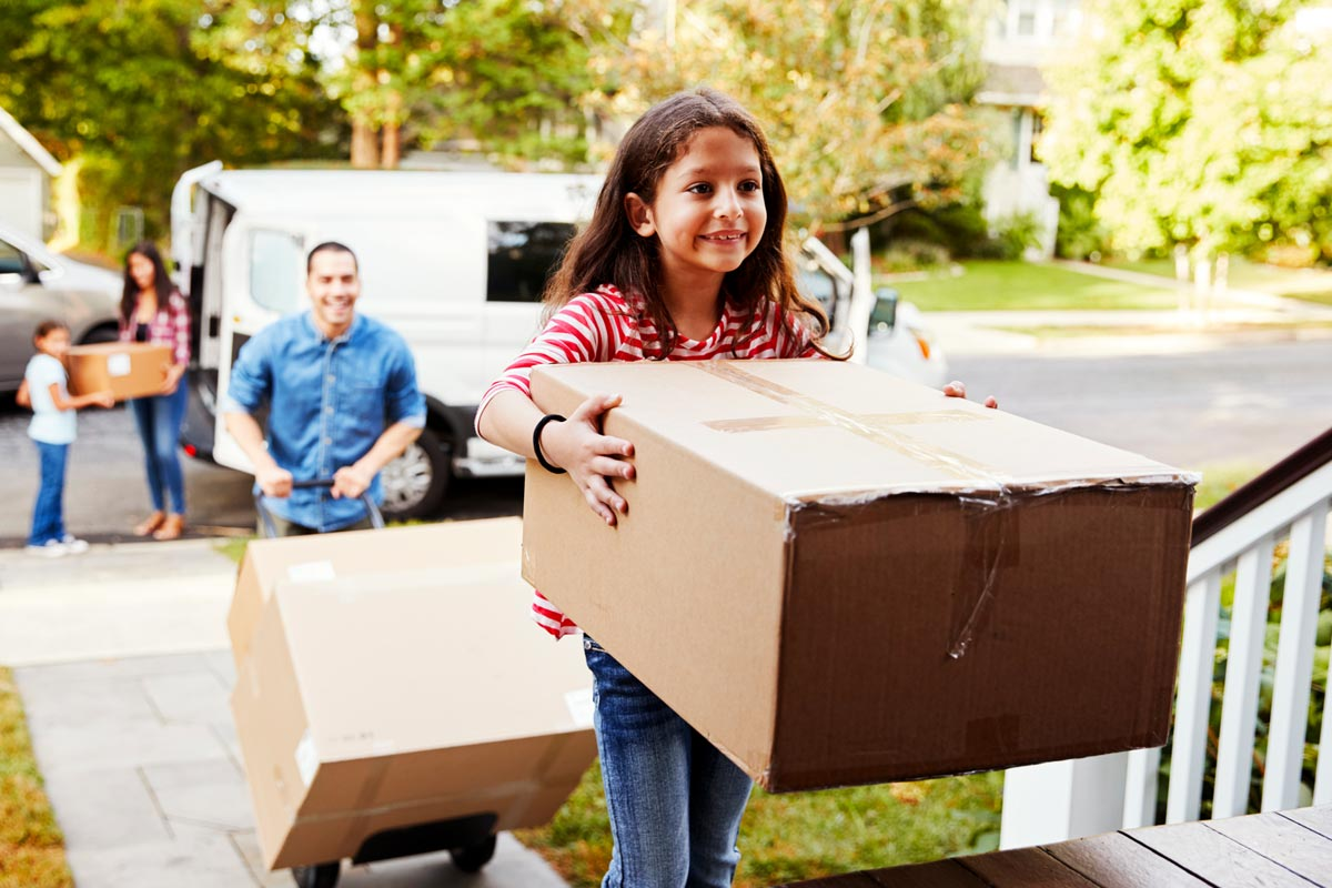 girl_carrying_box_into_new_home